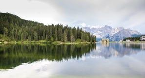 Озеро в Альпах где горные пики и древесины ели reflecte Стоковое Изображение RF