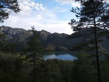 Озеро в горах окруженных лесом, Испанией стоковое изображение