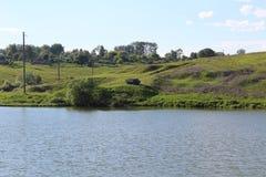 Озеро в хорошей погоде На противоположности банк тележка на которую рыболовы приехали Стоковое Изображение