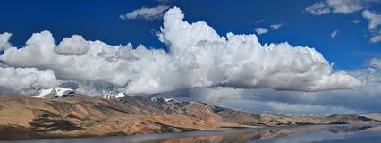 Озеро гор среди ярких оранжевых скалистых холмов, в облаках кумулюса голубого неба огромных белых, Гималаи, панорама фото Стоковая Фотография RF