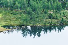 Озеро гор с камнями и деревьями на береге стоковая фотография rf