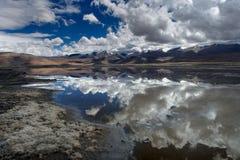 Озеро гор с поверхностью зеркала воды, в которой небо и горы симметрично отражены, на переднем плане sh Стоковые Фото