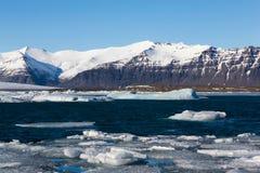 Озеро зимы Исландии с снегом покрыло предпосылку горы и неба ясности голубого Стоковое Изображение