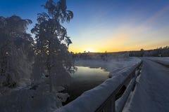 Озеро зим в Финляндии на заходе солнца Стоковая Фотография