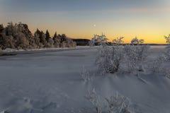 Озеро зим в Финляндии на заходе солнца Стоковое Фото
