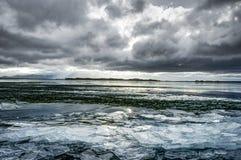 Озеро зим замерли ландшафтом, который с ледяными полями и облачное небо в Ic Стоковые Изображения
