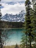 Озеро и снег покрыли горы на бурный день Стоковое Изображение RF