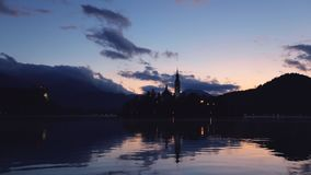 Озеро кровоточенное с церковью St Marys предположения на небольшом острове на заходе солнца; Кровоточенный, Словения, Европа акции видеоматериалы