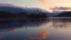 Озеро кровоточенное с церковью St Marys предположения на небольшом острове на заходе солнца; Кровоточенный, Словения, Европа видеоматериал
