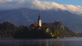 Озеро кровоточенное с церковью St Marys предположения на небольшом острове на заходе солнца; Кровоточенный, Словения, Европа сток-видео
