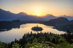 Озеро кровоточило Словению Красивый восход солнца над кровоточенным озером с небольшой церковью паломничества Большинств известны стоковые изображения rf