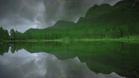 Озеро между горами и зелеными лесами отразило симметрично сток-видео