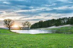 Озеро на заходе солнца в лесе среди зеленого луга и драматических облаков Стоковое фото RF