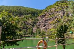 Озеро на ноге скалистой горы огражено с деревянной загородкой Вокруг газебо для остатков стоковое фото rf