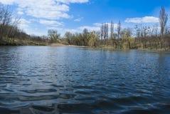 Озеро под голубым небом. Стоковые Фото
