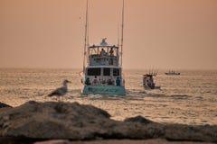 озеро рыболовства рыболова около времени захода солнца к стоковое фото