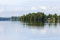 Озеро, сочный лес и немного домов в Финляндии Стоковое Изображение RF
