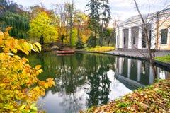 Озеро с мостом и шлюпкой в парке Стоковая Фотография