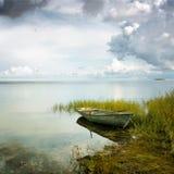 Озеро с сиротливой шлюпкой стоковое фото rf