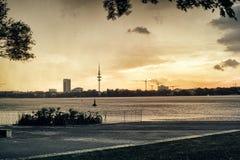Озеро Alster в людей парка города башни ТВ взгляда Гамбурга Германии ноче неба панорамы плавания известных гребя стоковое фото