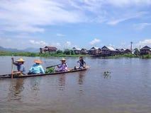 ОЗЕРО INLE, МЬЯНМА - 26-ОЕ МАЯ 2014: Местные люди на шлюпке longtail перед плавая деревней на озере Inle Стоковая Фотография RF