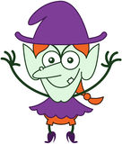 Озорная ведьма хеллоуина представляя и усмехаясь злоумышленно Стоковое Изображение