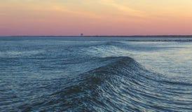 Океанская волна на заходе солнца стоковые изображения