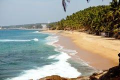 Океанская волна с скалистыми скалами и пальмами Стоковая Фотография RF