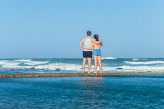 Океанские волны мальчика девушки наблюдая Стоковая Фотография