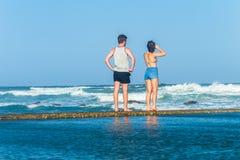 Океанские волны мальчика девушки наблюдая Стоковая Фотография RF