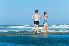Океанские волны мальчика девушки наблюдая Стоковое Изображение