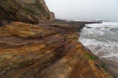 Океанские волны пропуская вниз на striped утесах берега Стоковые Фото