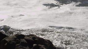 Океанские волны разбивают в пляж и скалистые скалы акции видеоматериалы