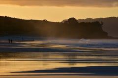 Океанский пляж с прибоем на заходе солнца Стоковые Фотографии RF