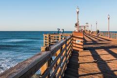 Океан взгляда людей от пристани рыбной ловли берега океана на ясном утре Стоковая Фотография RF