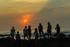 Океан восхода солнца пляжа девушек Silhouetted мальчиками Стоковые Изображения