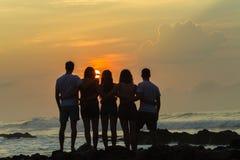 Океан восхода солнца пляжа девушек Silhouetted мальчиками Стоковое фото RF