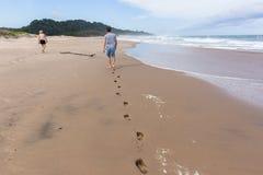 Океан пляжа следов ноги мальчика девушки идя Стоковая Фотография