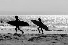 Океан Surfboards девушек Silhouetted пляжем Стоковое Фото