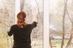 Окна молодой женщины моя стоковая фотография