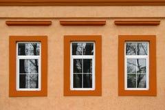 3 окна на оранжевой стене Стоковое Изображение