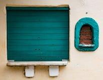2 окна, одного взошли на борт вверх с голубой древесиной и другое bricked Стоковые Фото