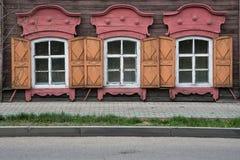 3 окна с деревянным высекаенным architrave в старом деревянном доме в старом русском городке стоковые фотографии rf