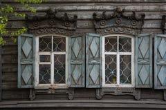 2 окна с деревянным высекаенным architrave в старом деревянном доме в старом русском городке стоковое фото