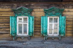 2 окна с деревянным высекаенным architrave в старом деревянном доме в старом русском городке стоковое фото rf