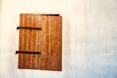 Окно Брайна красное деревянное с заржаветым металлом прикрепляет на петлях на детали стены белого цемента Стоковые Фотографии RF