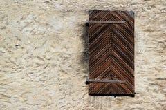 Окно в старой каменной стене закрыло с деревянными штарками Стоковое Фото