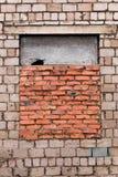 Окно закладывано кирпичами Окно положенный кирпич Серая кирпичная стена с окном положенным с красным кирпичом Окно полу-закрыто стоковая фотография