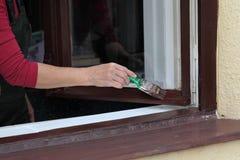 Окно краски женского работника деревянное для того чтобы коричневеть цвет, старую реновацию окна дома стоковые фотографии rf
