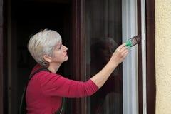 Окно краски женского работника деревянное для того чтобы коричневеть цвет, старую реновацию окна дома стоковое фото rf